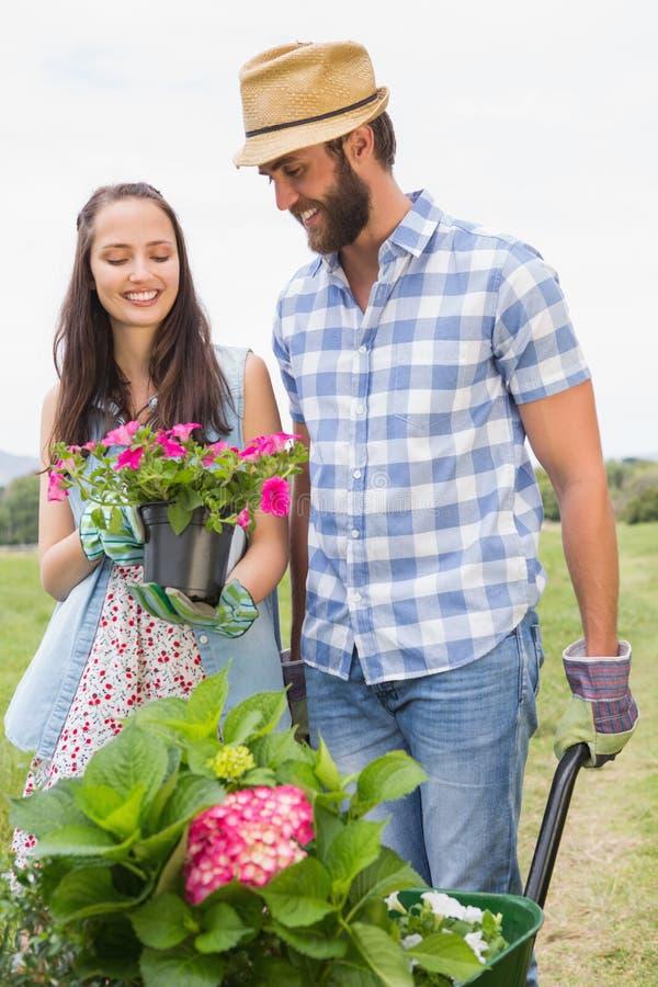 Pares novos felizes que jardinam junto fotos de stock