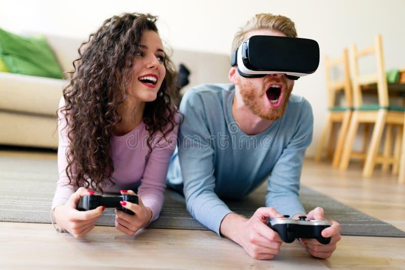 Pares novos felizes que jogam jogos de vídeo com os auriculares da realidade virtual fotografia de stock royalty free