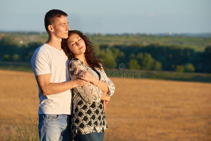 Pares novos felizes que levantam altamente no país exterior, conceito romântico dos povos, temporada de verão imagens de stock royalty free