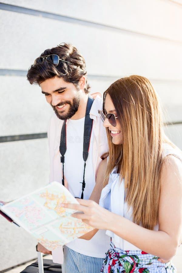Pares novos felizes que olham o mapa da cidade, viajando no exterior imagens de stock royalty free