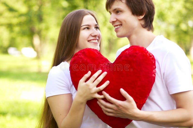 Pares novos felizes que prendem o coração vermelho grande fotografia de stock