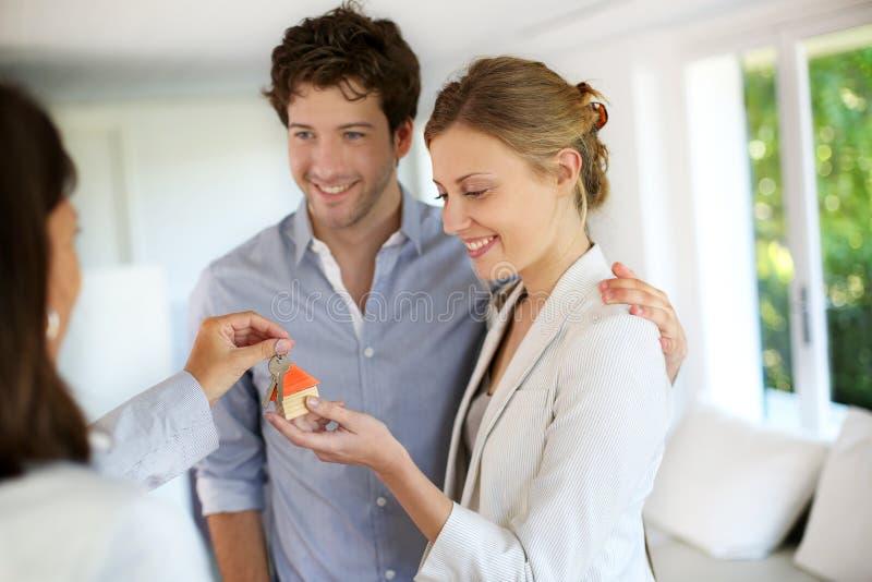 Pares novos felizes que recebem chaves de sua casa nova foto de stock royalty free