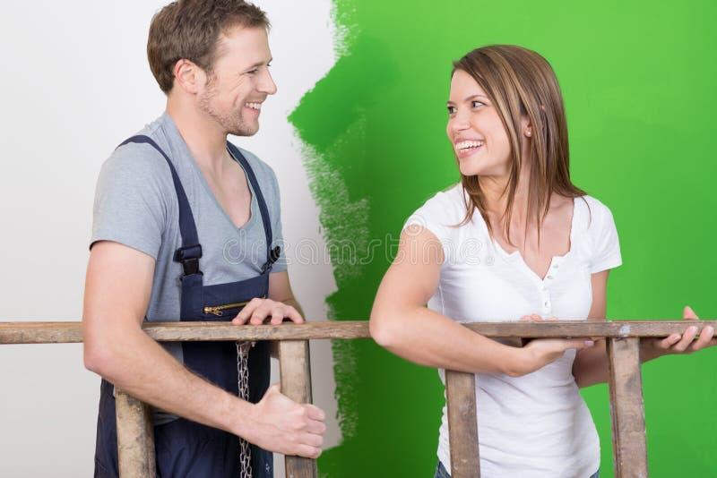 Pares novos felizes que riem como redecoram fotos de stock royalty free