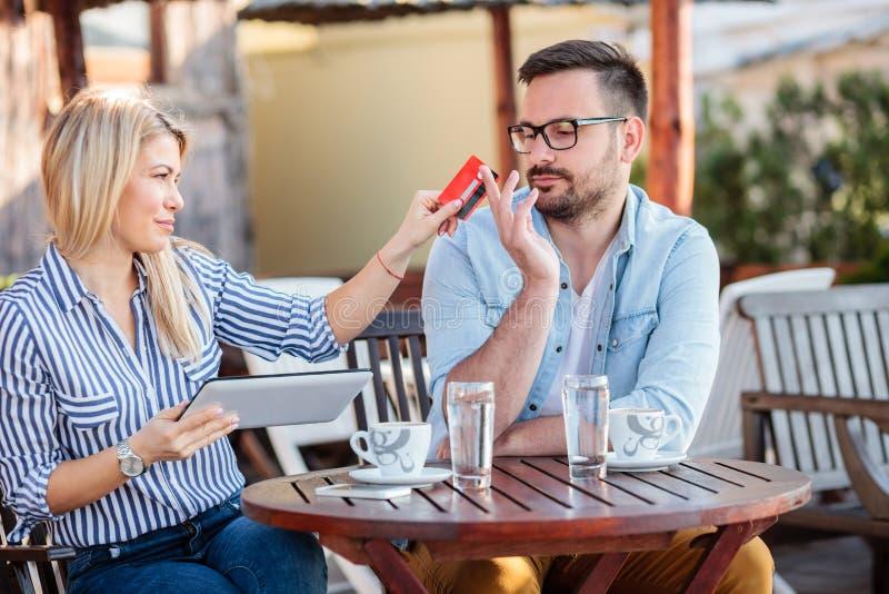 Pares novos felizes que sentam-se em um caf? e que compram em linha fotografia de stock