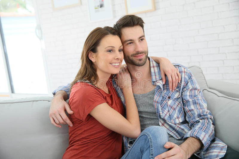 Pares novos felizes que sentam-se em um sofá imagens de stock