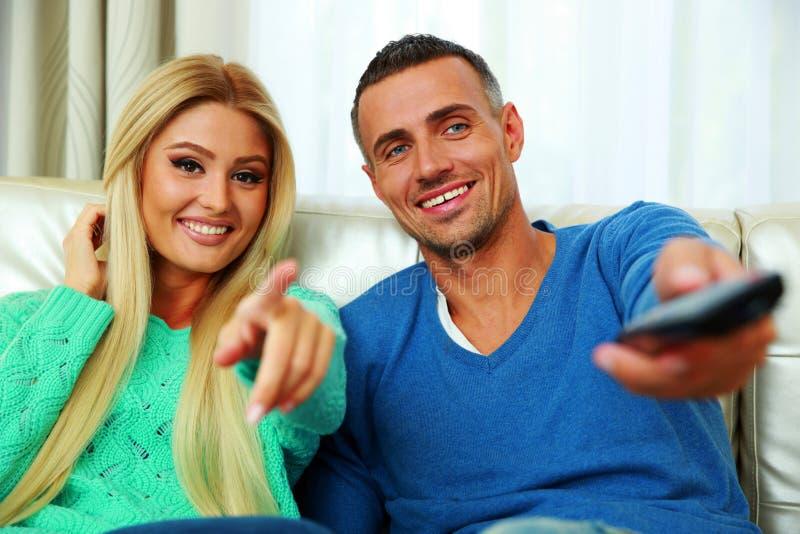 Pares novos felizes que sentam-se no sofá imagem de stock royalty free