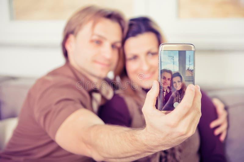 Pares novos felizes que sentam-se no sofá e que fazem o selfie imagens de stock royalty free