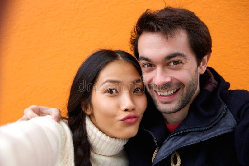 Pares novos felizes que sorriem e que tomam o selfie imagens de stock royalty free