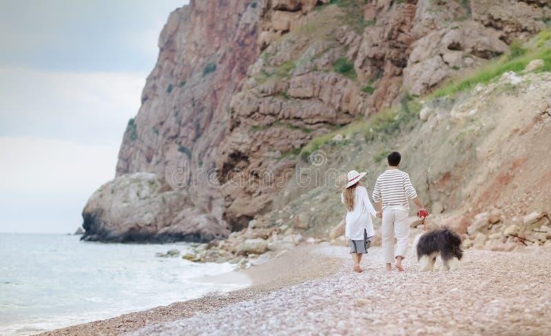 Pares novos felizes que têm o divertimento da praia em feriados do curso da lua de mel das férias fotografia de stock
