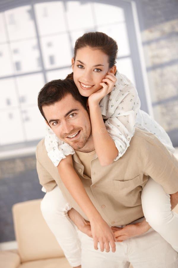 Pares novos felizes que têm o divertimento em casa imagens de stock royalty free