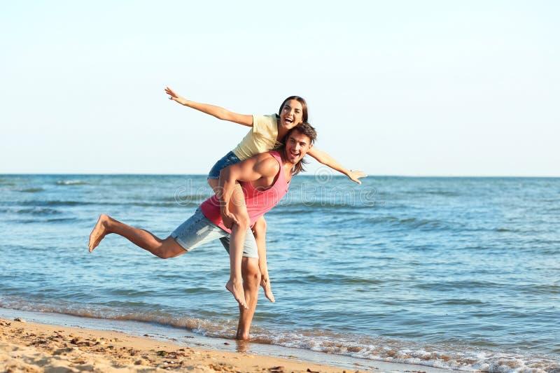 Pares novos felizes que têm o divertimento na praia fotografia de stock
