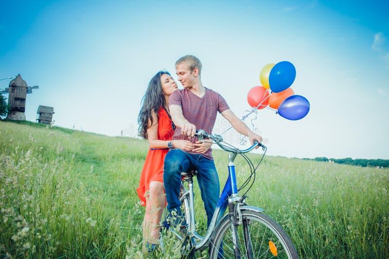Pares novos felizes que têm o divertimento que vai fora para um passeio com a bicicleta no campo foto de stock royalty free