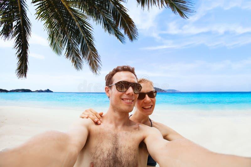 Pares novos felizes que tomam a foto do selfie na praia foto de stock royalty free