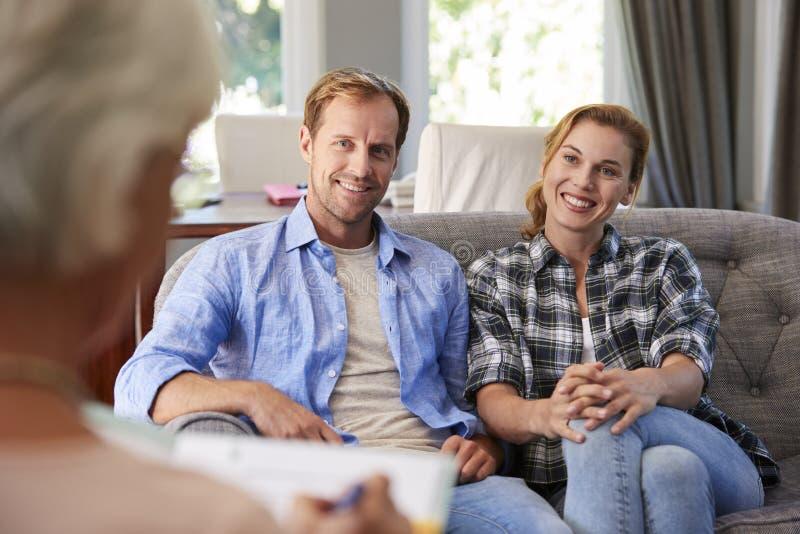 Pares novos felizes que tomam o conselho financeiro em casa imagens de stock