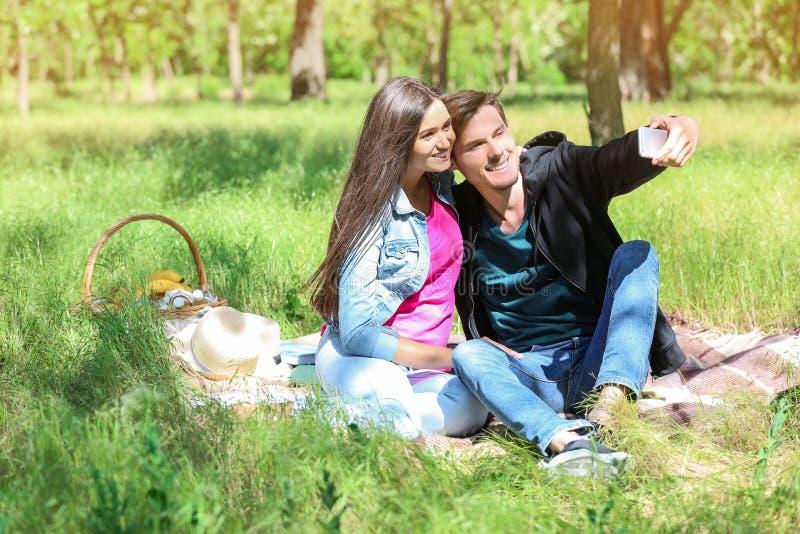 Pares novos felizes que tomam o selfie no parque verde fotografia de stock royalty free