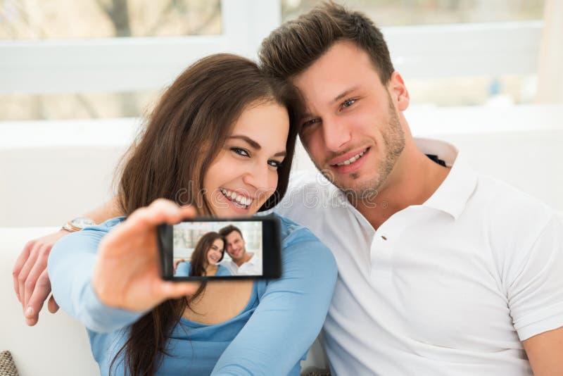 Pares novos felizes que tomam um selfie fotografia de stock