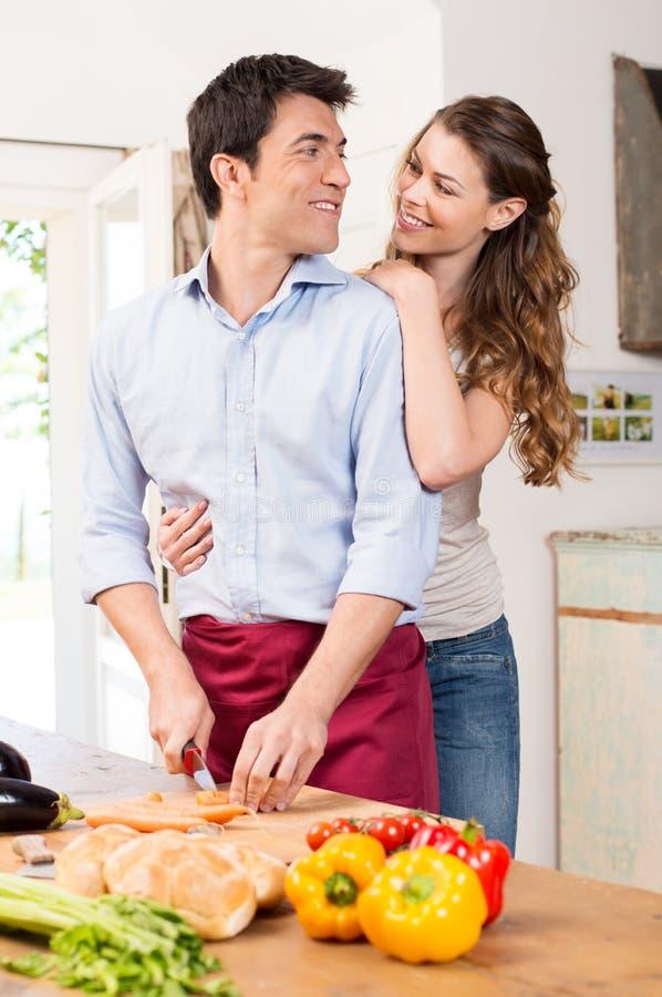 Pares novos felizes que trabalham na cozinha imagem de stock