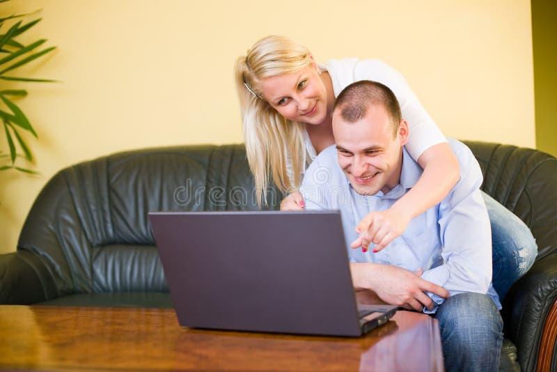 Pares novos felizes usando o portátil em casa. fotos de stock