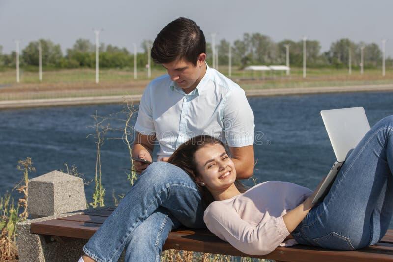 pares novos felizes usando o port?til ao sentar-se junto no parque imagem de stock