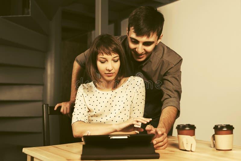 Pares novos felizes usando o tablet pc digital que senta-se na tabela fotos de stock royalty free