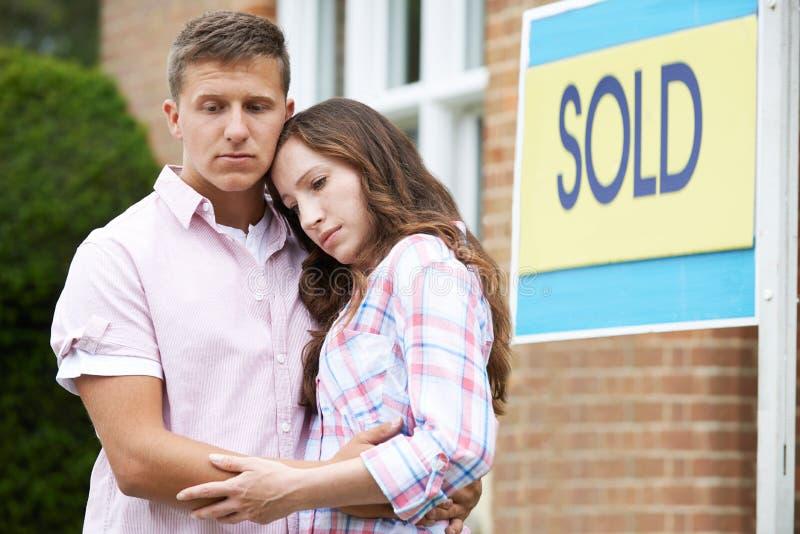 Pares novos forçados para vender em casa com os problemas financeiros fotografia de stock royalty free