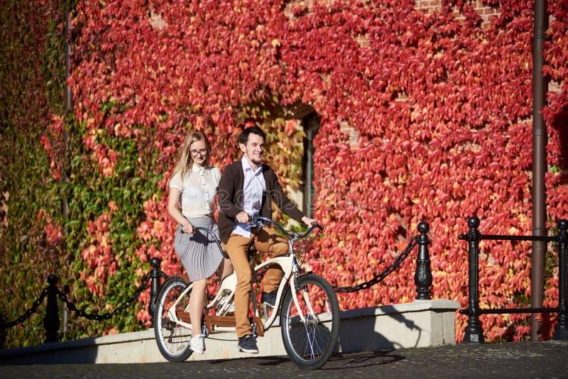 Pares novos, homem considerável e mulher loura dando um ciclo a bicicleta em tandem construindo coberto de vegetação com a hera v imagem de stock
