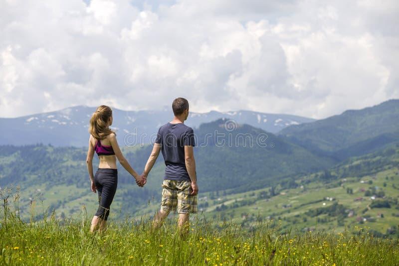 Pares novos, homem desportivo e mulher magro guardando as mãos fora no fundo da paisagem bonita da montanha no dia de verão ensol imagem de stock