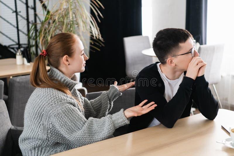 Pares novos infelizes que discutem, esposa irritada que olha o marido que responsabiliza o dos problemas, conflitos na união, má fotos de stock royalty free