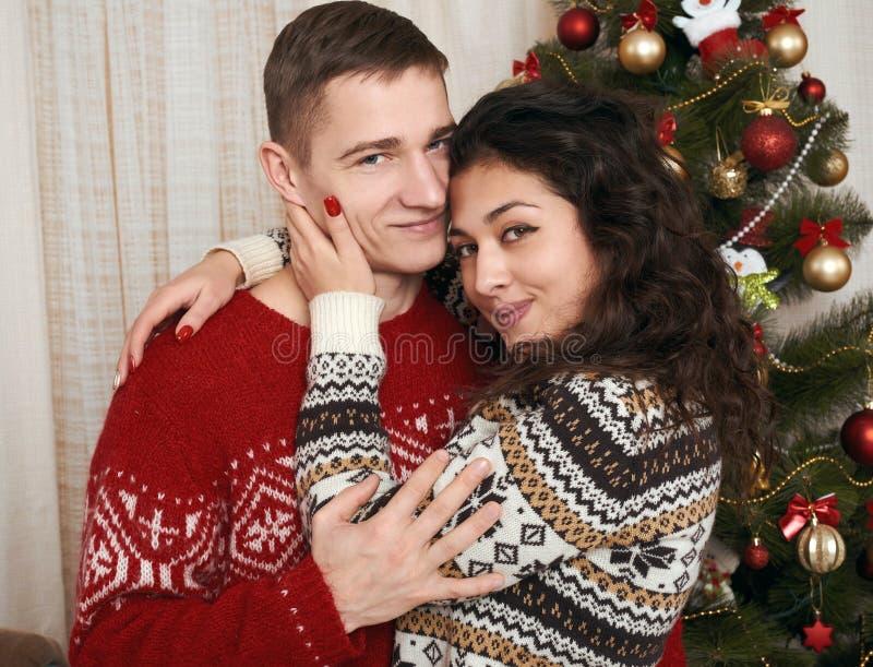Pares novos junto com a árvore de Natal no interior home - conceito do amor e do feriado, véspera do xmas fotos de stock