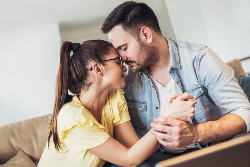 Pares novos loving que abraçam e que relaxam no sofá imagens de stock royalty free
