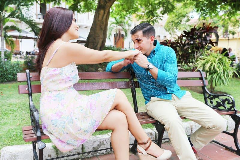 Pares novos loving que flertam ao sentar-se em um banco de parque imagem de stock