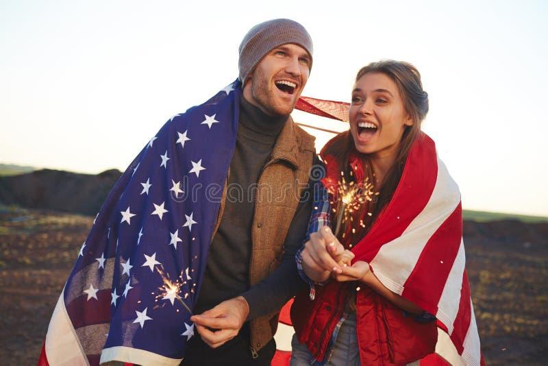 Pares novos modernos que comemoram América imagem de stock royalty free