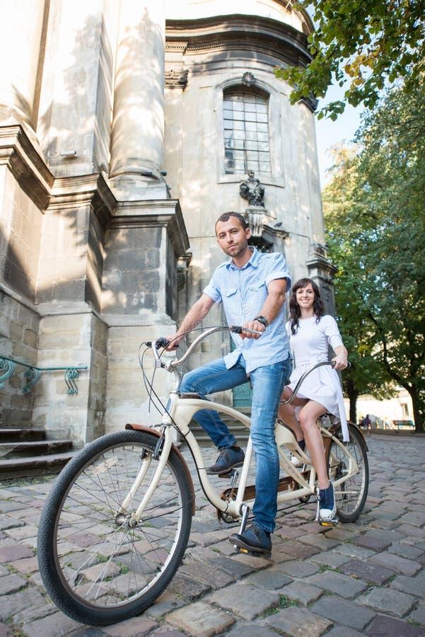 Pares novos na bicicleta em tandem retro na cidade da rua imagens de stock royalty free