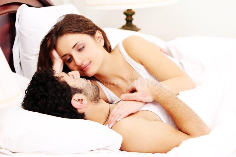 Pares novos na cama fotografia de stock royalty free