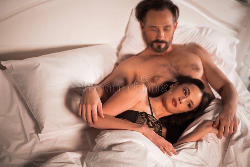 Pares novos na cama, cena romântica do amor no quarto foto de stock