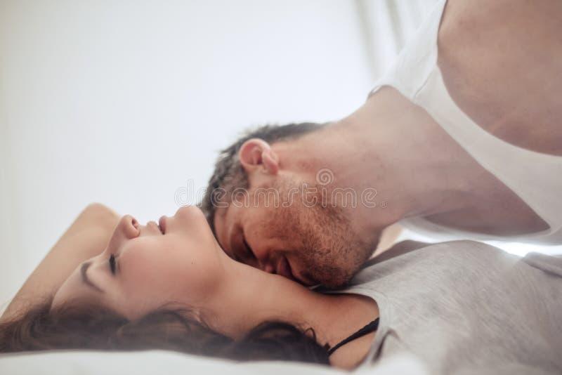 Pares novos na cama que aprecia preliminares românticas fotografia de stock