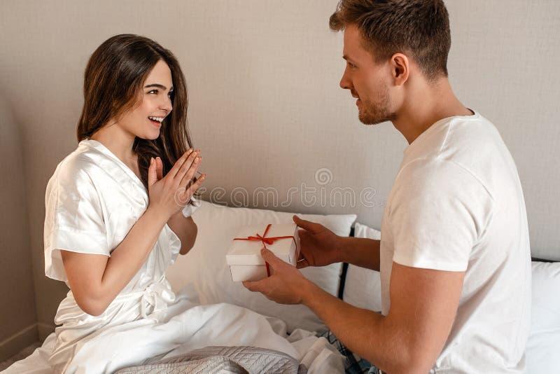 Pares novos na cama Um homem atrativo está dando o presente a sua amiga feliz, romance em um relacionamento foto de stock royalty free