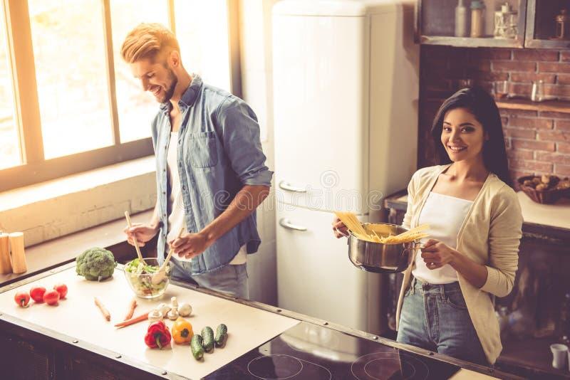 Pares novos na cozinha imagem de stock