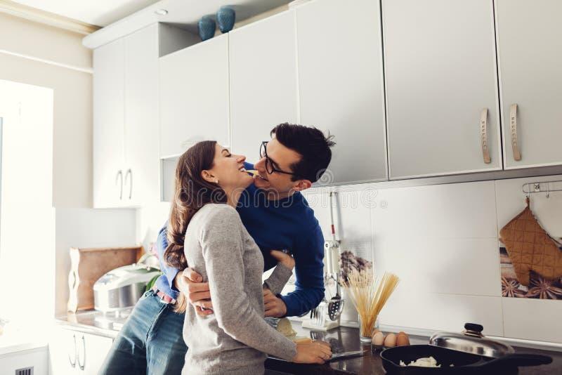 Pares novos na cozinha que abraça e que come o queijo imagens de stock
