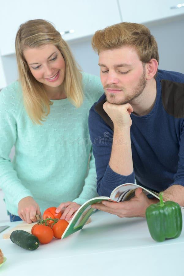 Pares novos na cozinha que prepara o almoço fotografia de stock royalty free