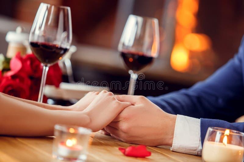 Pares novos na data no vinho bebendo de assento do restaurante que mantém as mãos macias fotos de stock royalty free