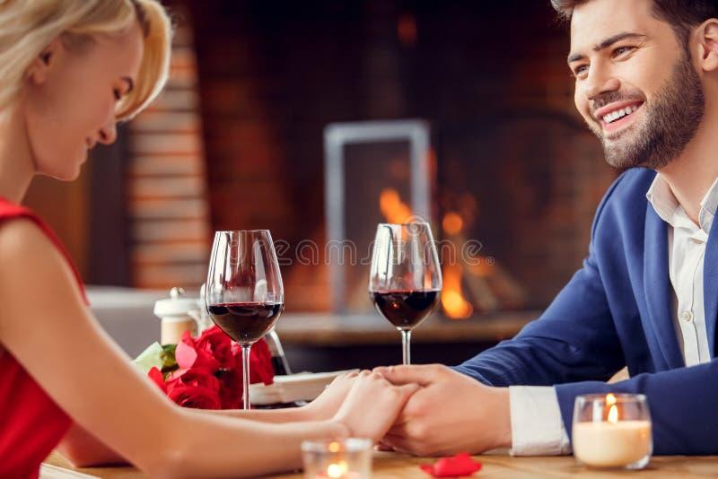 Pares novos na data no vinho bebendo de assento do restaurante que mantém a fala das mãos alegre imagem de stock royalty free