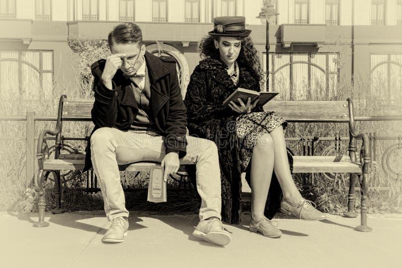 Pares novos na discussão que senta-se no banco na cidade velha fotos de stock