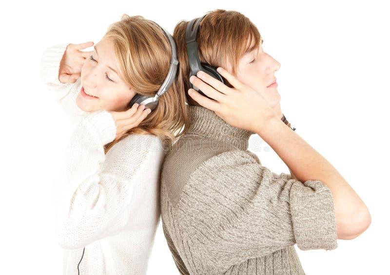 Pares novos na música de escuta dos auscultadores imagem de stock