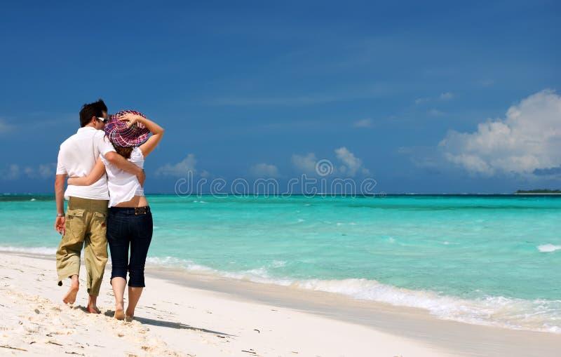 Pares novos na praia foto de stock
