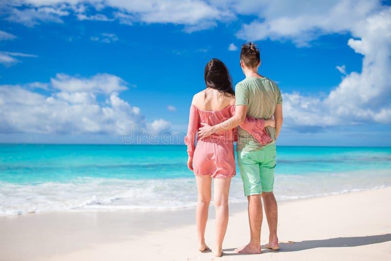 Pares novos na praia branca durante férias de verão A família feliz aprecia sua lua de mel imagens de stock