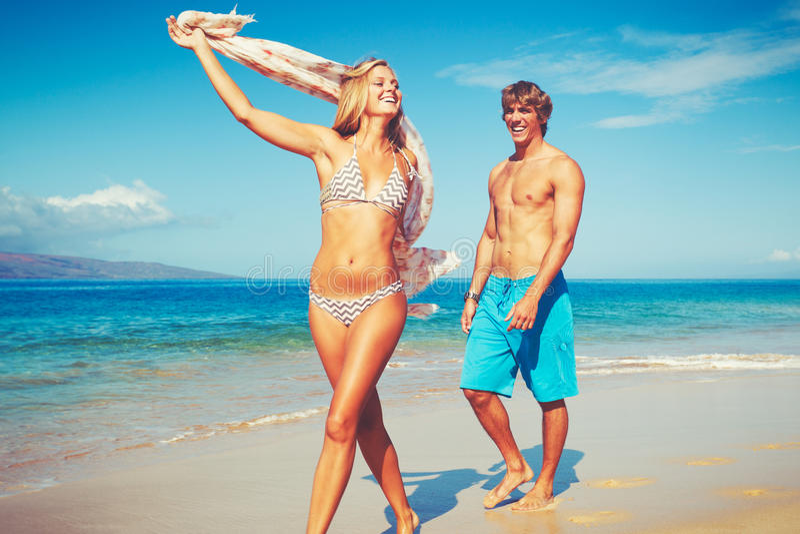 Pares novos na praia tropical imagens de stock