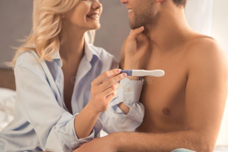 Pares novos na verificação do teste de gravidez da cama imagens de stock