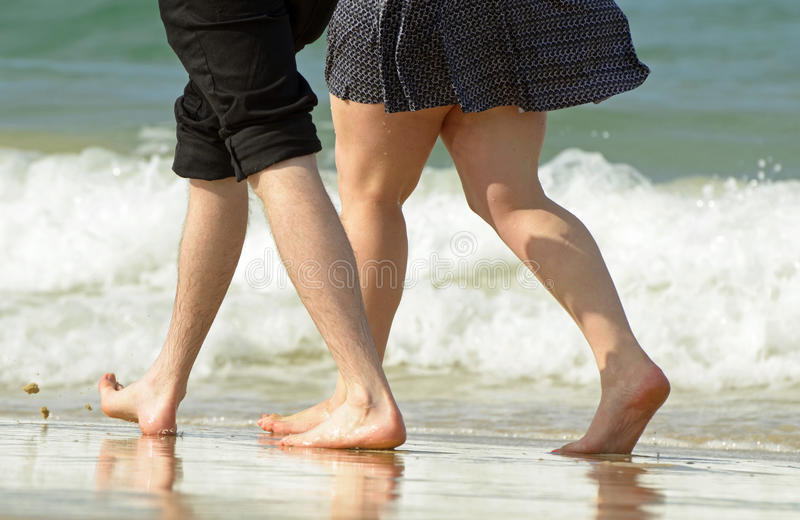 Pares novos nas férias que andam ao longo da borda das águas do oceano foto de stock