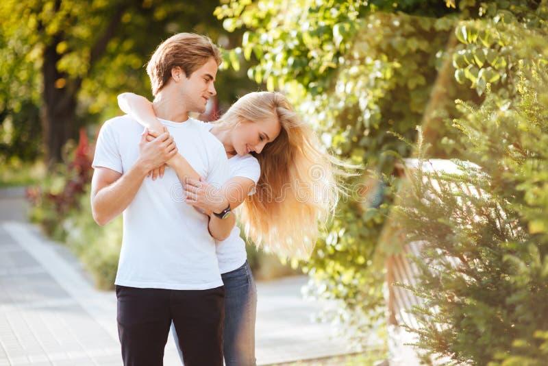 Pares novos no amor, abraçando na rua fotos de stock